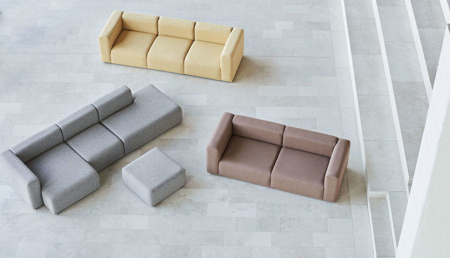 Overhead view of a gray Mags Ottoman, placed in a large, open room with gray, yellow, and red Mags Sectional Sofas.
