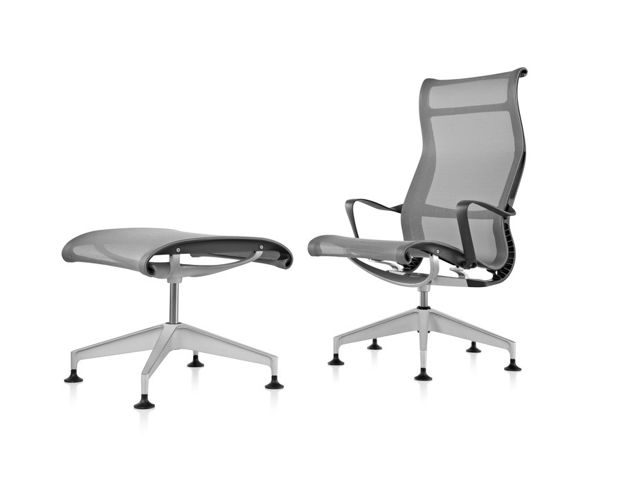 A black Setu Lounge Chair and Ottoman featuring a suspension seat and back, viewed from a 45-degree angle.
