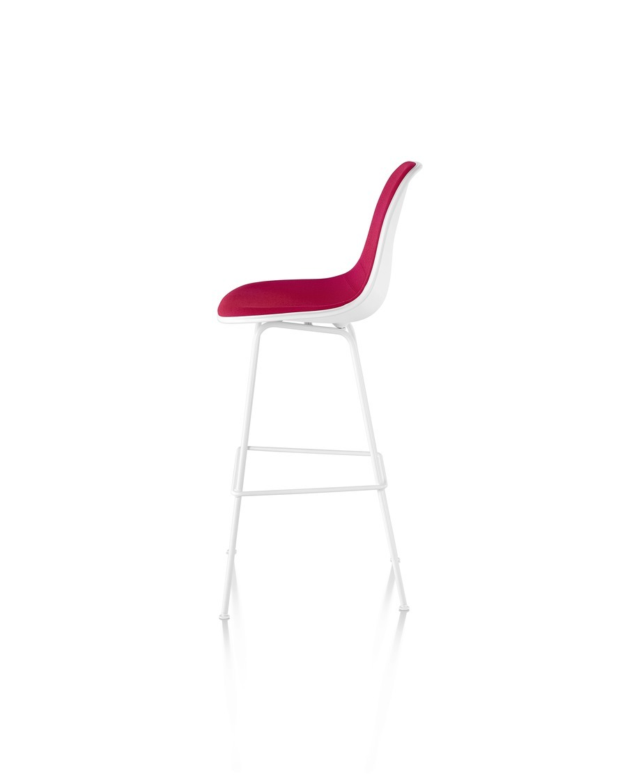 White Eames Molded Plastic Stool with red upholstery, viewed from the side