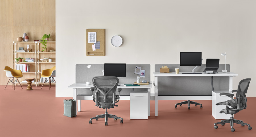 office setting with Nevi Link system with white work surfaces, Aeron chairs, lounge area in background. One of the four desks is raised to standing height