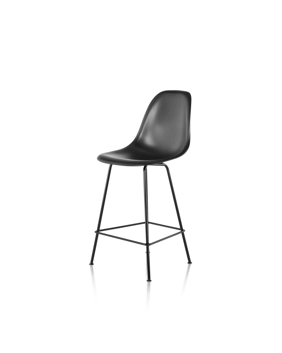 Three-quarter rear view of a black Eames Molded Wood Stool with black legs.