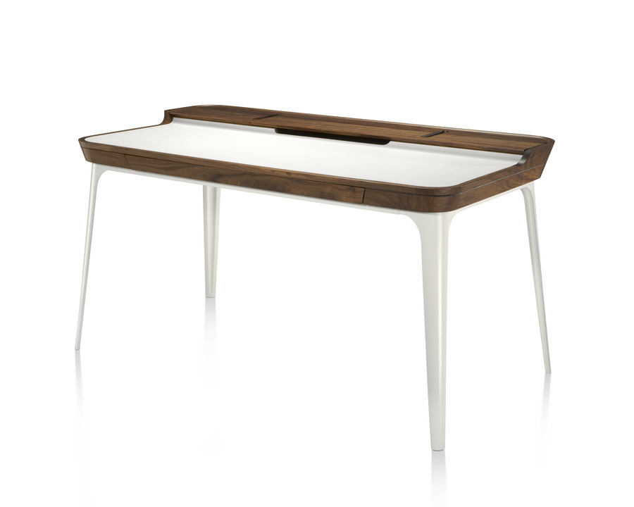 Modern Airia home office desk from Herman Miller in white with dark wood trim and white legs in three quarter view.