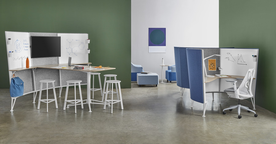 A Prospect Media Space with inspirational materials on the desk and sketches on the whiteboards near two Prospect Solo spaces with white Sayl Chairs.