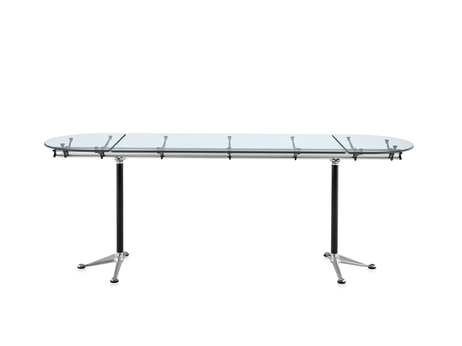 Oval Burdick table with a glass top, white leg columns, and aluminum bases viewed from the long side
