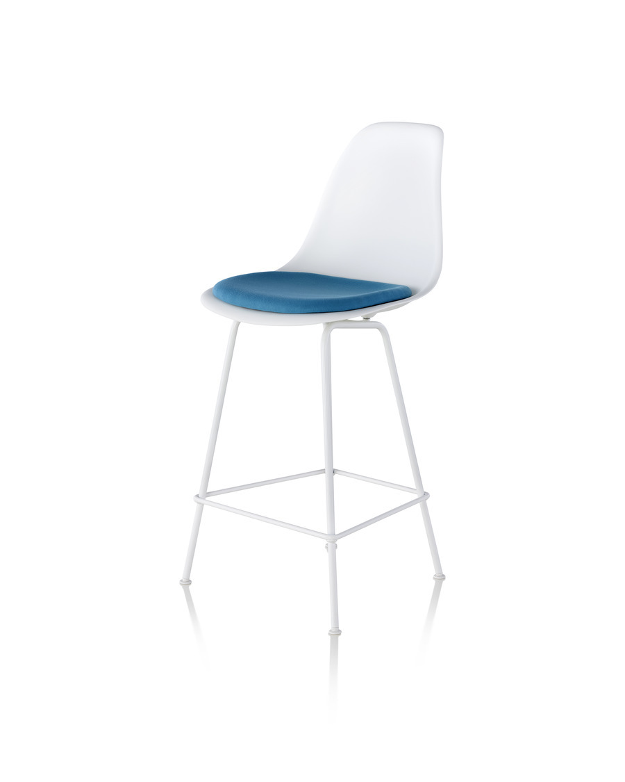 Angled front view of a white Eames Molded Plastic Stool with blue upholstery.