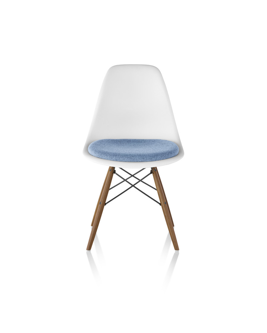 White Eames Molded Plastic side chair with a light blue upholstered seat pad and dowel legs, viewed from the front.