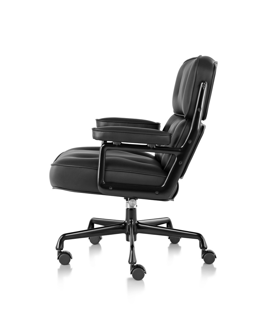 Profile view of a black leather Eames Executive Chair, showing the thickly cushioned seat, back, and arms, on wheels