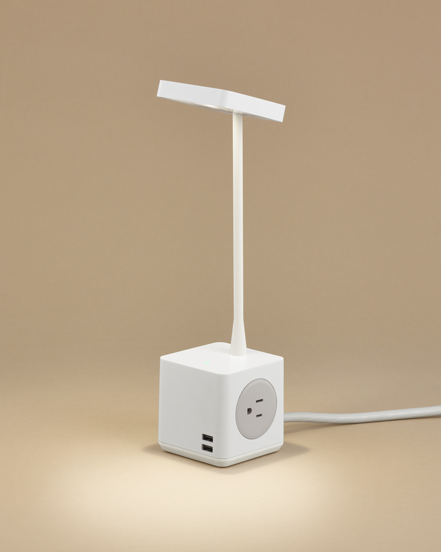 Angled view of a compact Cubert Personal Light, showing two USB ports and one power outlet in the base.
