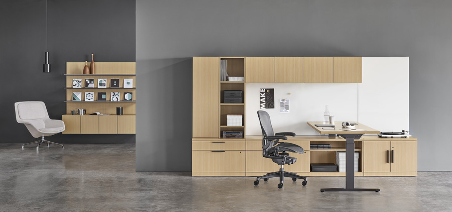 A Canvas Private Office with light wood storage, a standing desk positioned at sitting height, a black Aeron office chair, and a gray Striad lounge chair.