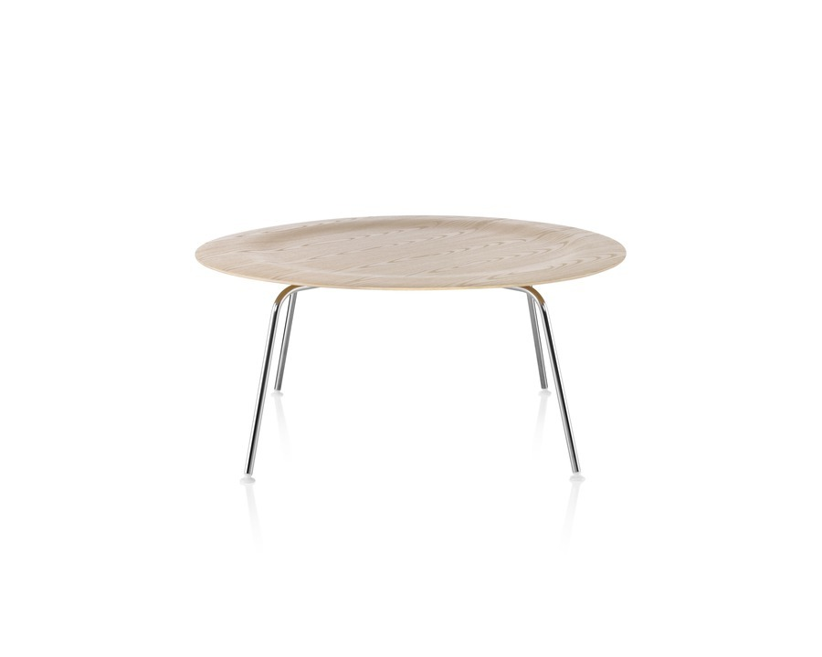 A round Eames Molded Plywood Coffee Table with metal legs and an indented top in a light finish.