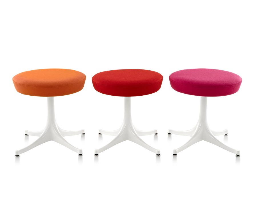 Three Nelson Pedestal Stools with orange, red, and pink upholstered seats and white bases.