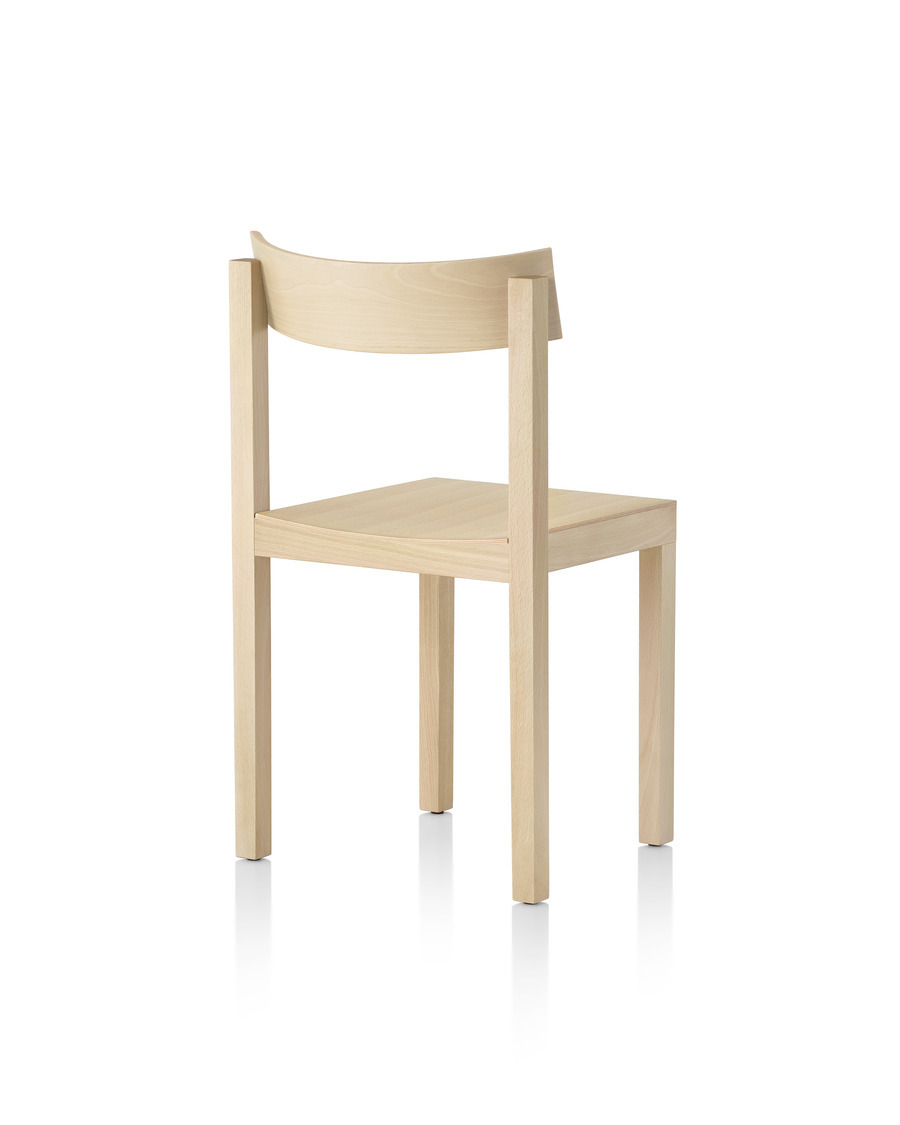 Three-quarter rear view of a Mattiazzi Primo stacking chair with a light wood finish.