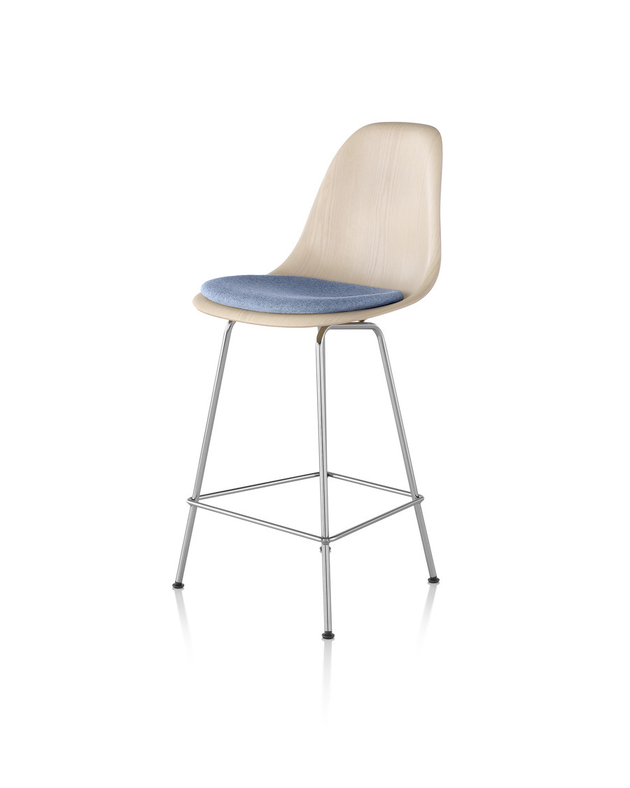 Eames Molded Wood Stool with a light finish, light blue seat pad, and silver legs, viewed from a 45-degree angle.