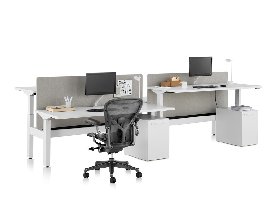 Nevi Link standing desk with black Aeron office chair, privacy screens, monitors, and rectangular work surfaces. 2 of the 4 desks raised to standing height