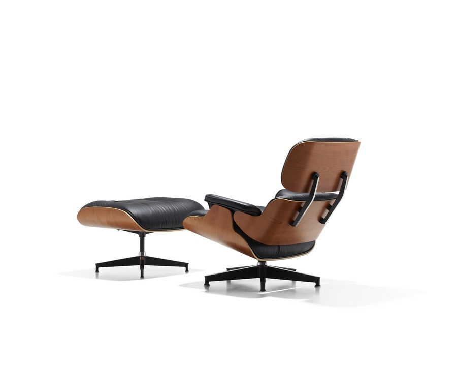 Angled rear view of black leather Eames Lounge Chair and Ottoman with wood paneling on back and sides of furniture pieces