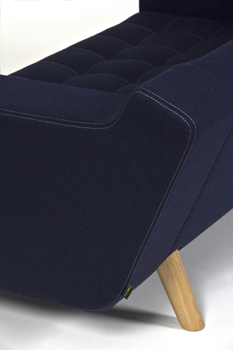 A close-up view from the side of a navy naughtone Portion Sofa with solid walnut legs and white stitching.