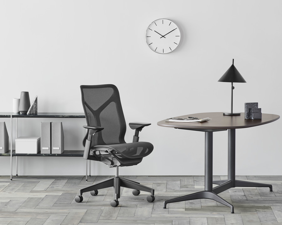 Black mid back Cosm office chair featured in small home office setting surrounded by desk, lamp, and shelving unit