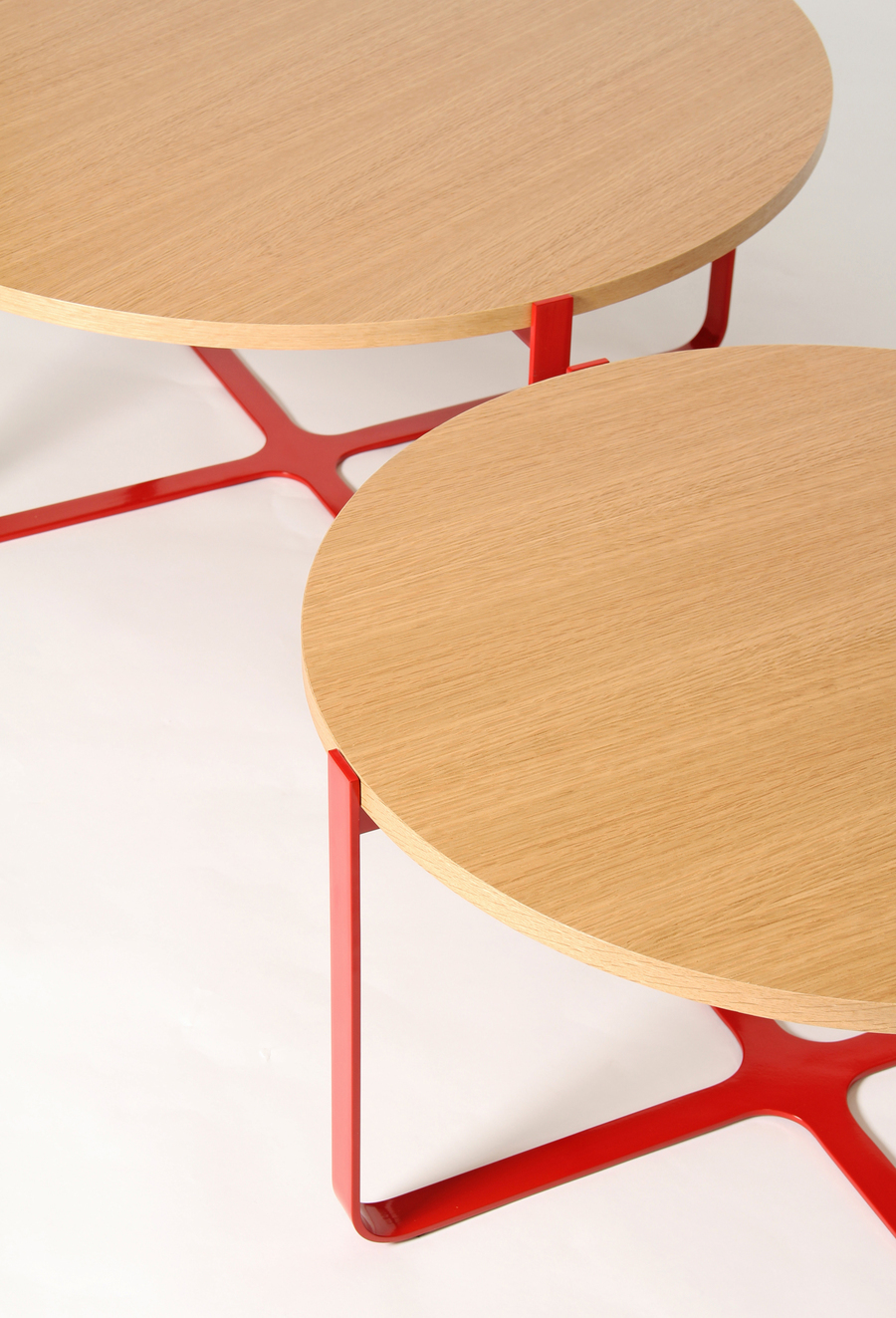 A close-up view of two red, round Trace Coffee Tables with wooden tops.