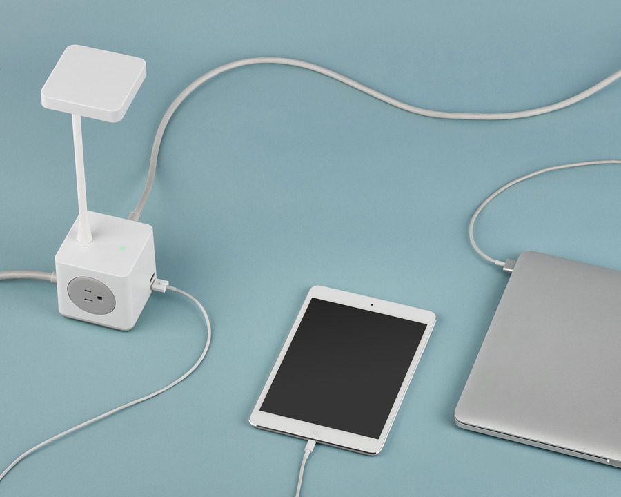 A compact Cubert Personal Light provides illumination while charging a tablet and notebook computer.