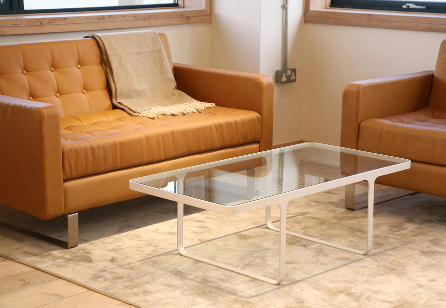 A white naughtone Trace Coffee Table with glass top in front of a leather Clyde Sofa and Clyde Club Chair.