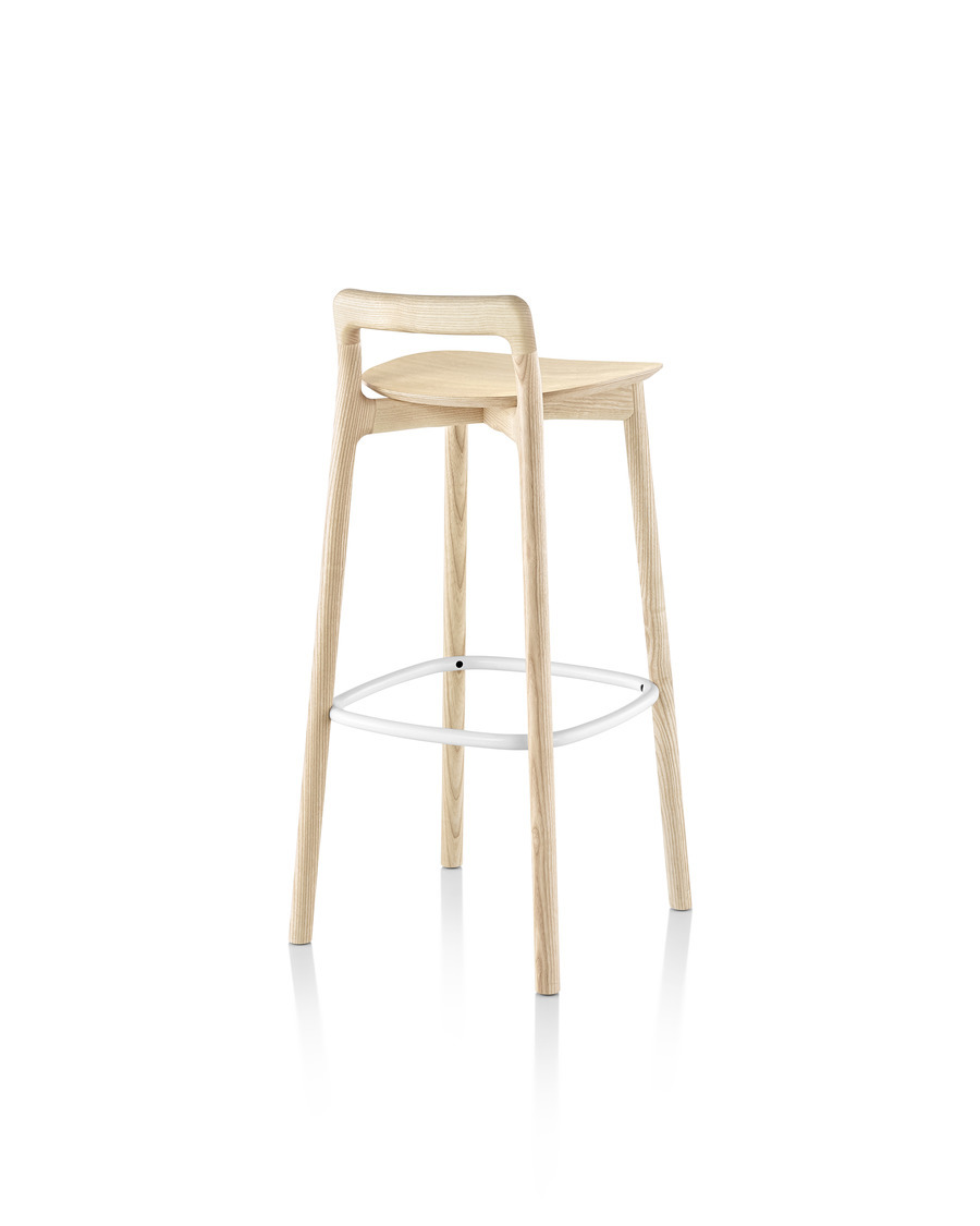 Three-quarter rear view of a Mattiazzi Branca Stool with a light wood finish and white footrest.