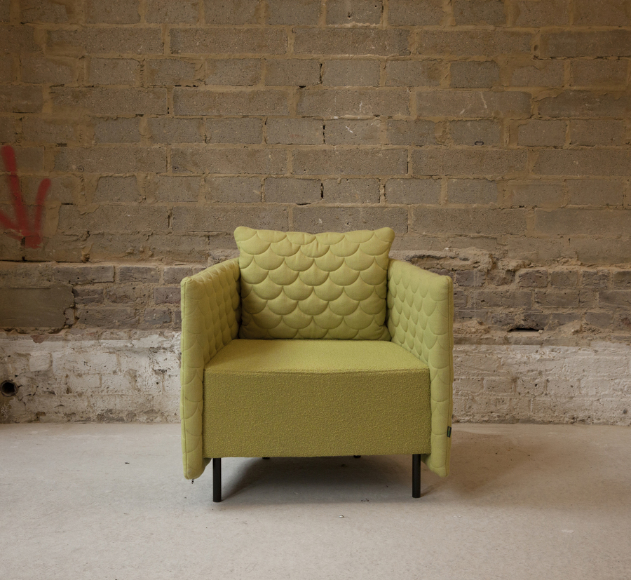 A front view of a naughtone Cloud Quilt Armchair upholstered in olive green, positioned in front of an unfinished brick and concrete block wall.