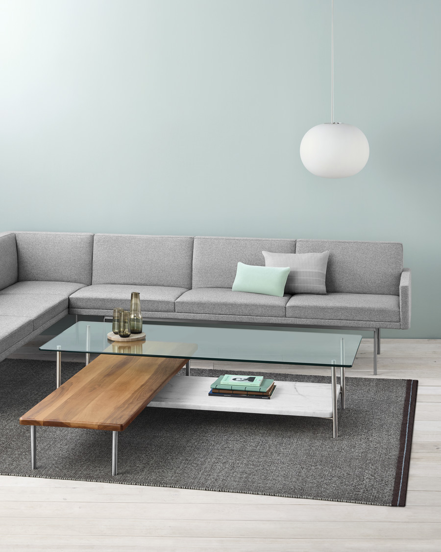 Glass and wood layer accent table showcased in living room with heather grey couch