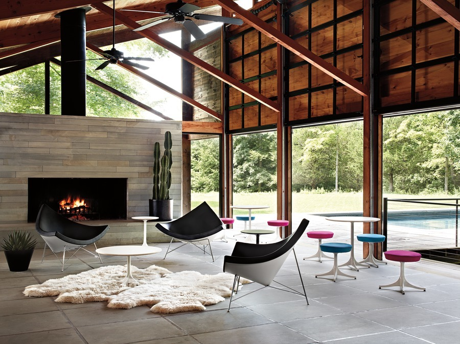 Three black leather Nelson Coconut Lounge Chairs and several Nelson Pedestal Stools in a glass-walled room with a fireplace.