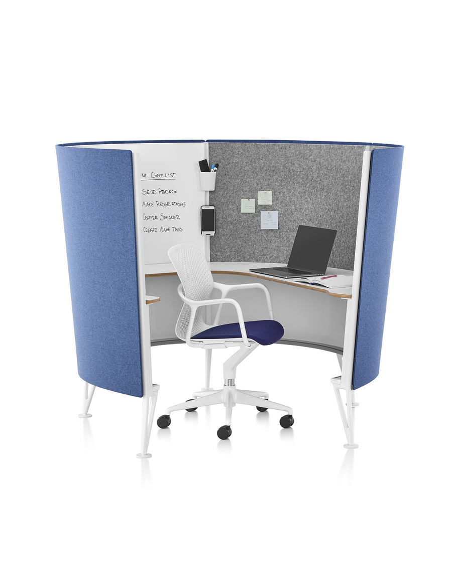 A Keyn desk chair with white frame and dark blue upholstered seat pad in a Prospect Solo Space with blue exterior acoustic fabric.
