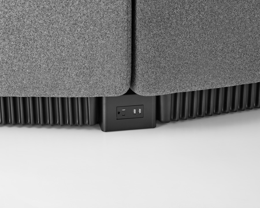 Close view of the base of connecting Chadwick Modular Seating modules, showing a receptacle with an outlet and two USB ports.