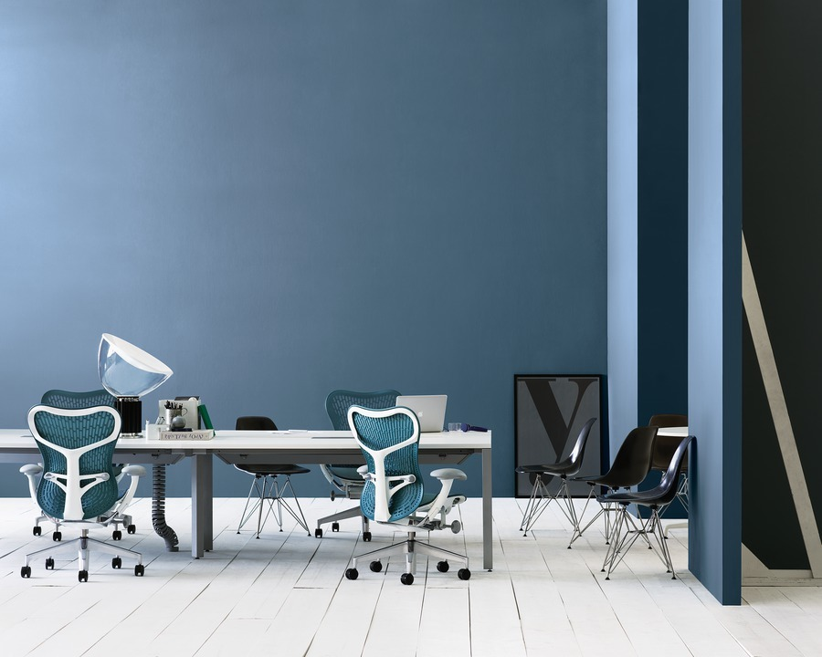 Blue Mirra 2 office chairs and black Caper Stacking Chairs in a video conferencing area featuring a Layout Studio benching system.