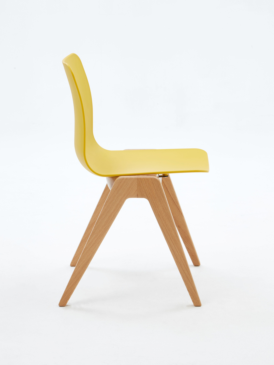 A yellow naughtone Polly Wood Chair with an oak base, viewed from the side.