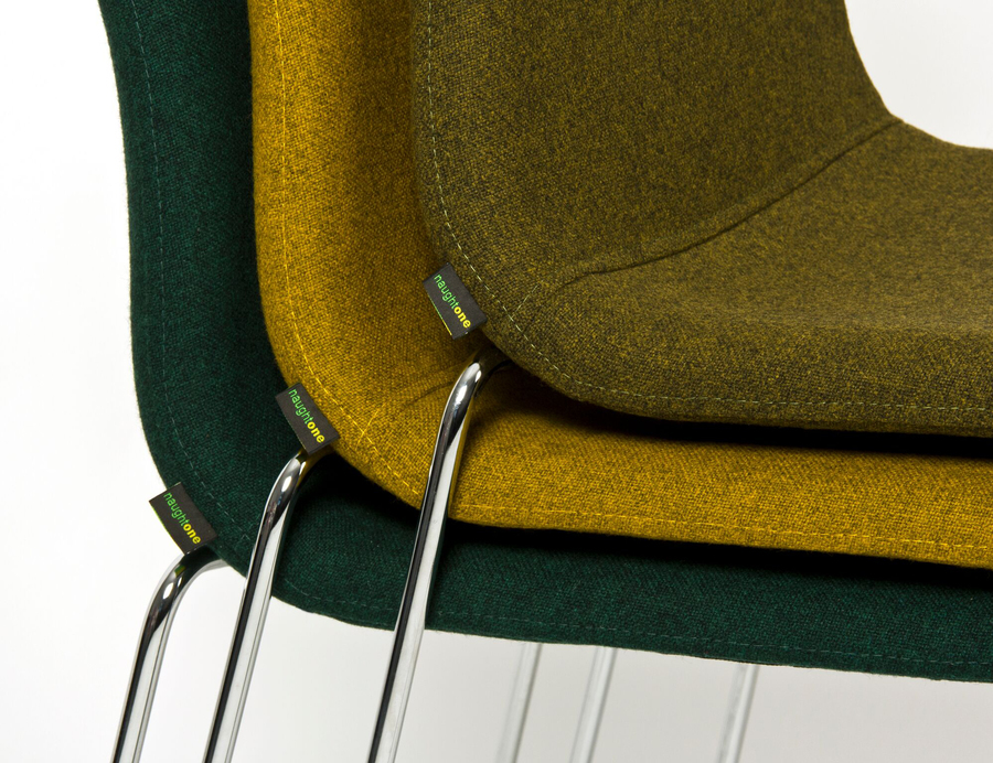 A close-up view from the side of three naughtone Viv Side Chairs stacked on top of one another in dark green, yellow, and light green.
