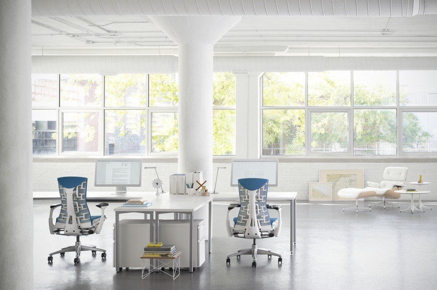 Two blue and white Embody office chairs sitting at white Everywhere Tables in a bright open office space with a wall of windows
