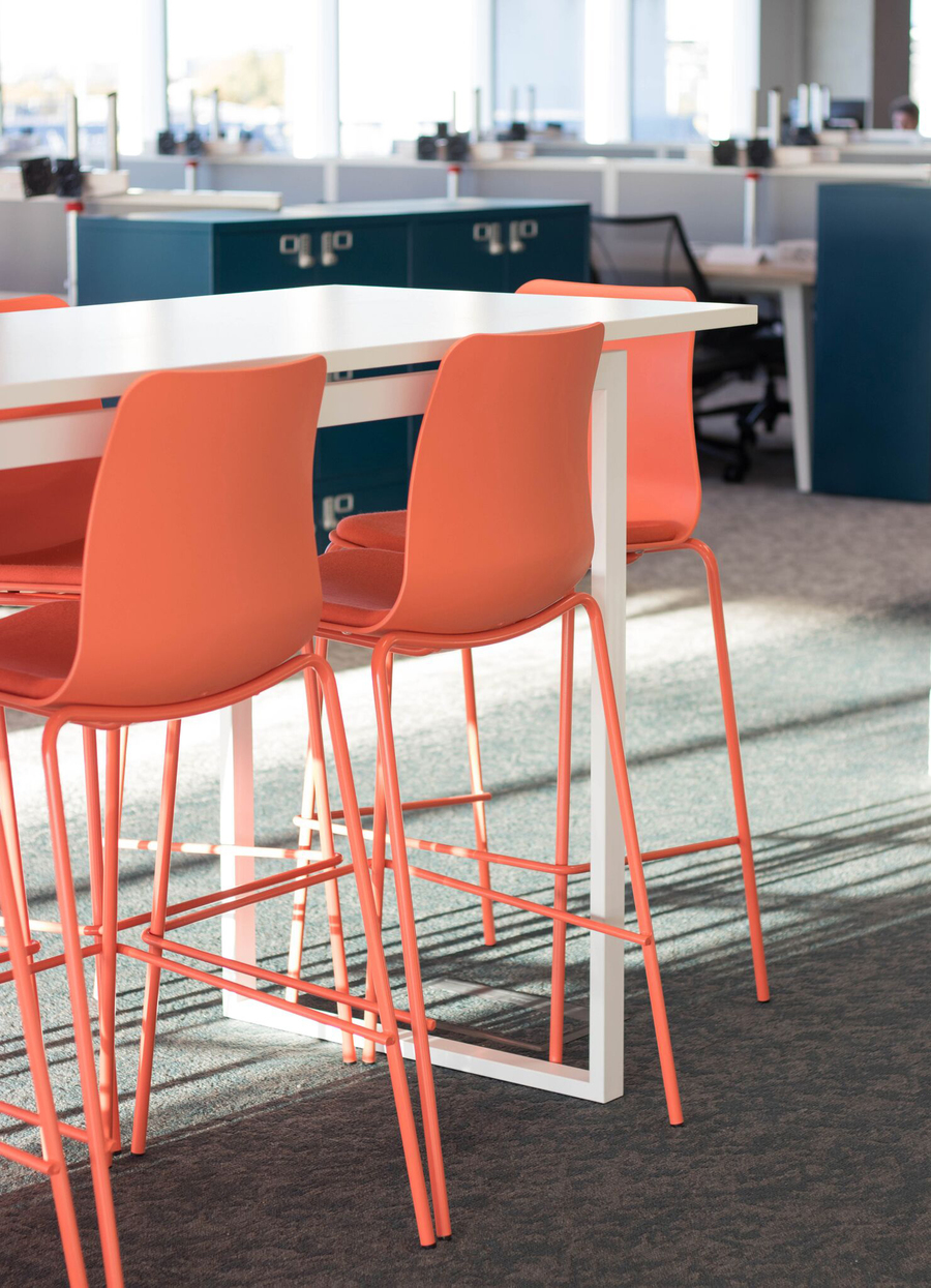 A close-up view of orange Polly Stools at a white bar height table in an office setting.