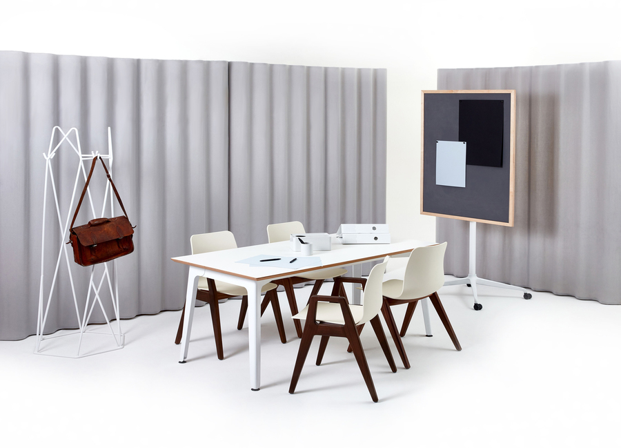 Five off-white Polly Wood Chairs with walnut bases and armrests placed at a white Fold Conference Table.