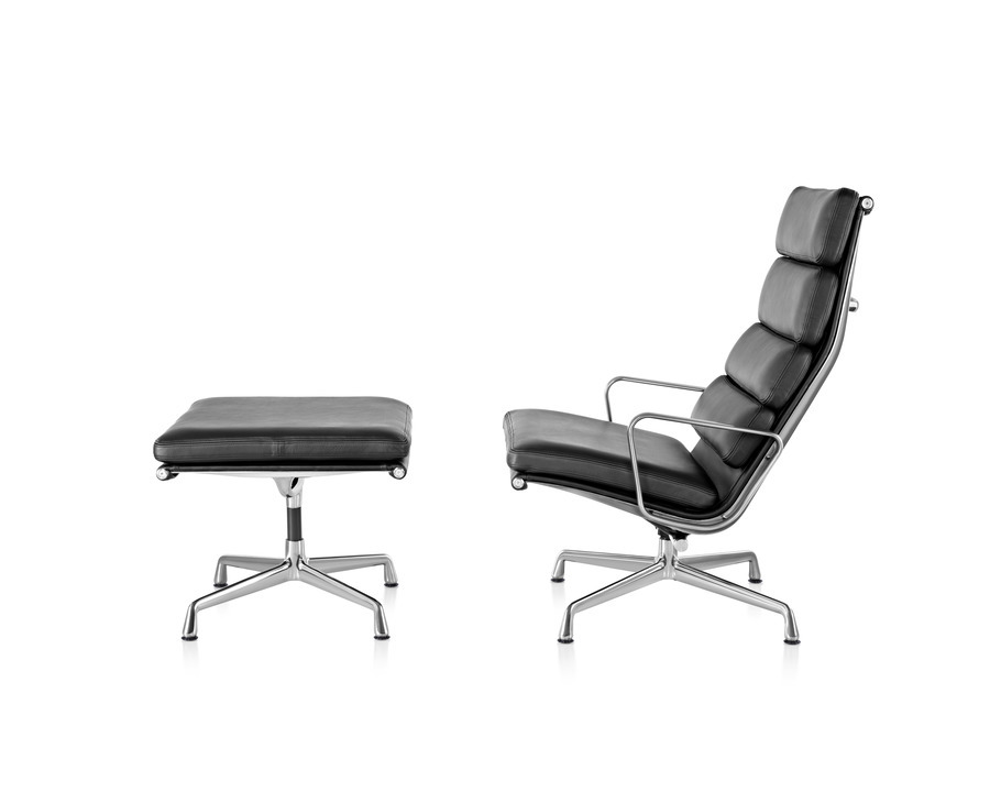 Profile view of black leather Eames Soft Pad chair with polished aluminum base and armrests, accompanied by a matching black leather ottoman