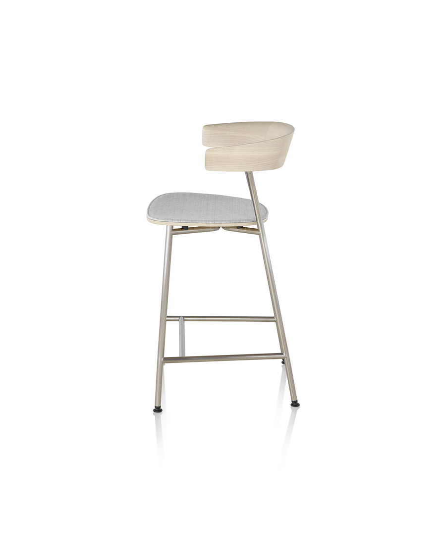 A metal base Leeway Stool with light wood backrest and upholstered seat, viewed from the side
