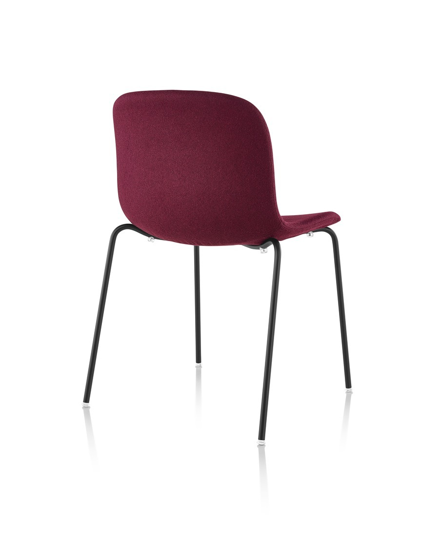 Three-quarter rear view of an armless Magis Troy Upholstered side chair in red fabric.