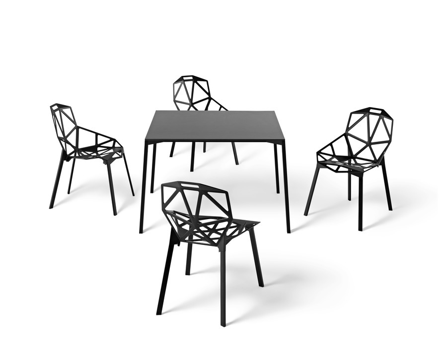 A black Magis Table_One Outdoor table with a square top, surrounded by four black Magis Chair_One side chairs.