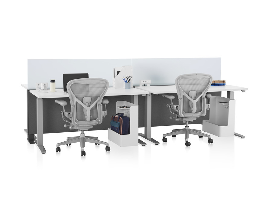 Canvas Channel in grey with glass screens, white Motia height-adjustable tables, lower bag storage, and light grey Aeron office chairs.