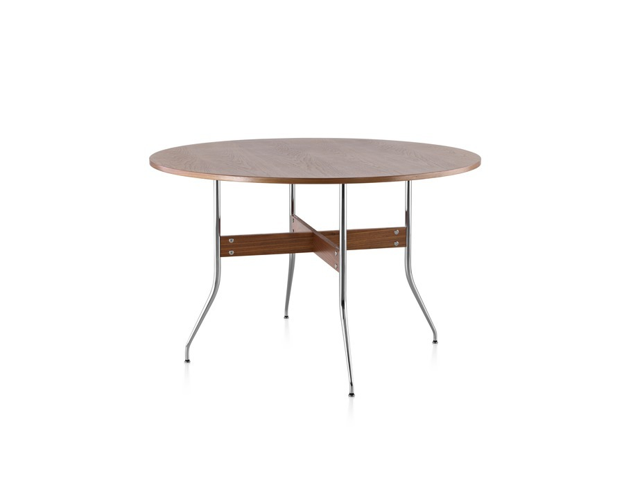 A round Nelson Swag Leg Table in a medium wood finish, showing X-shaped walnut stretchers between tubular steel legs.