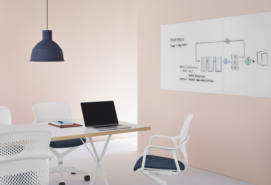 White Keyn Chairs with dark blue upholstery in a meeting space with a Glass White Board with brainstorming sketches on it at the end of a table.