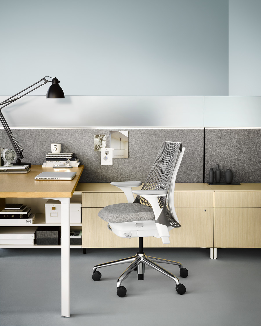 A Canvas Storage workstation in light wood with a grey screen and a white Sayl office chair.