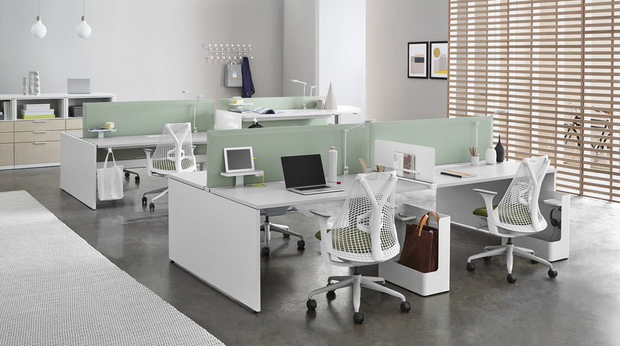 White Sayl Chairs with green upholstered seats at Layout Studio individual workstations with green dividing screens and white desk tops.