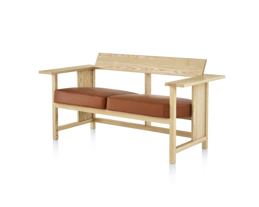 A Mattiazzi Clerici two-seat bench with orange cushions and a light wood finish, viewed from the front at a 45-degree angle.