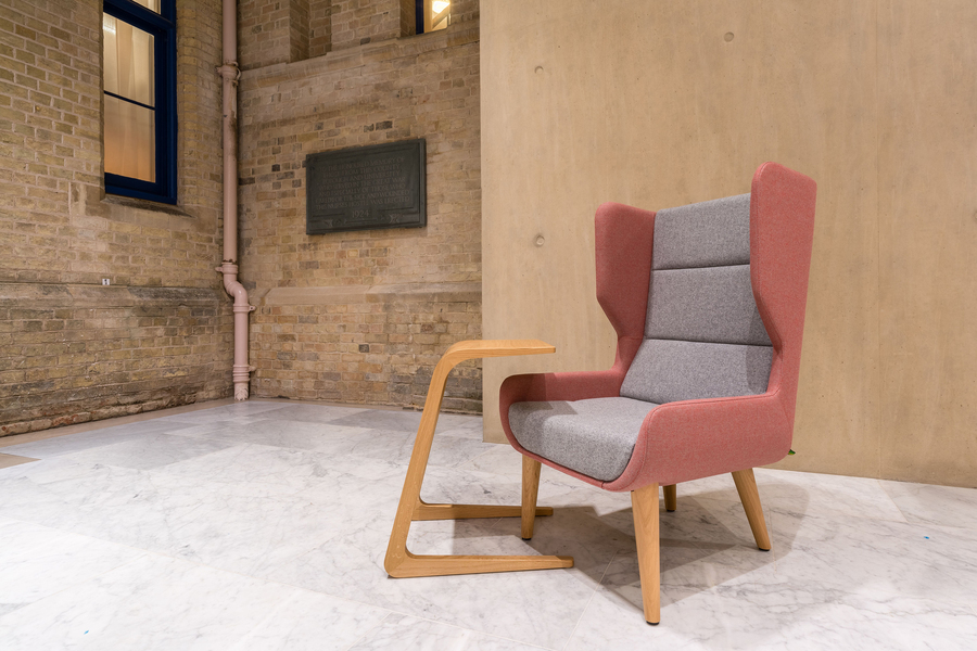A naughtone Hush Chair with a pink back and light gray seat padding and wooden base, viewed from the front at an angle and paired with a wood work table