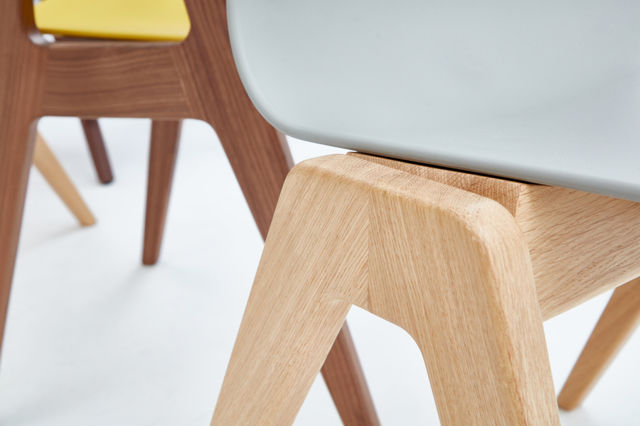 A close-up view of the oak base on a gray naughtone Polly Wood Chair.
