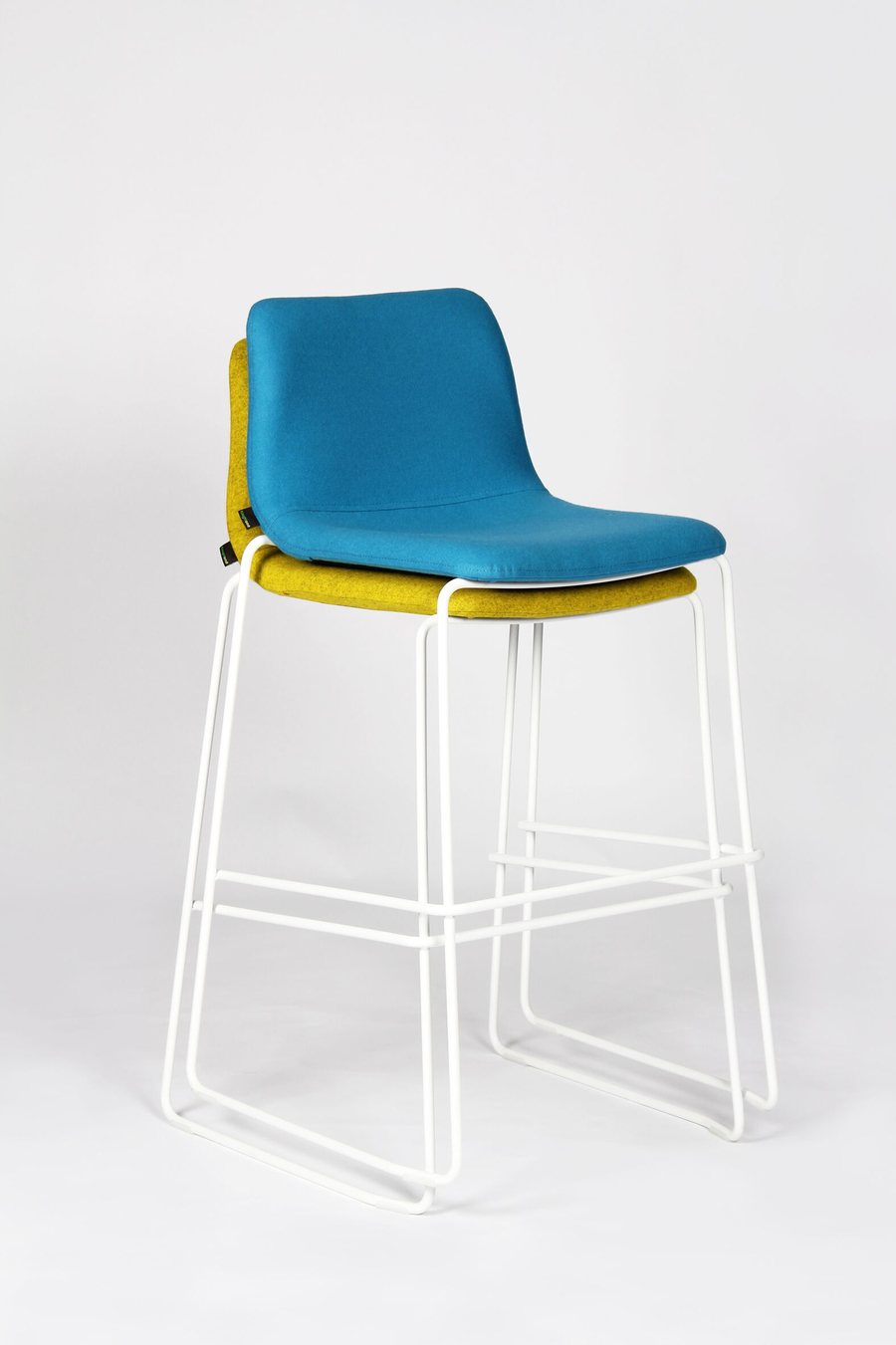 A blue Viv Stool with a white metal base stacked ontop of a green Viv Stool with a white metal base, viewed at an angle.