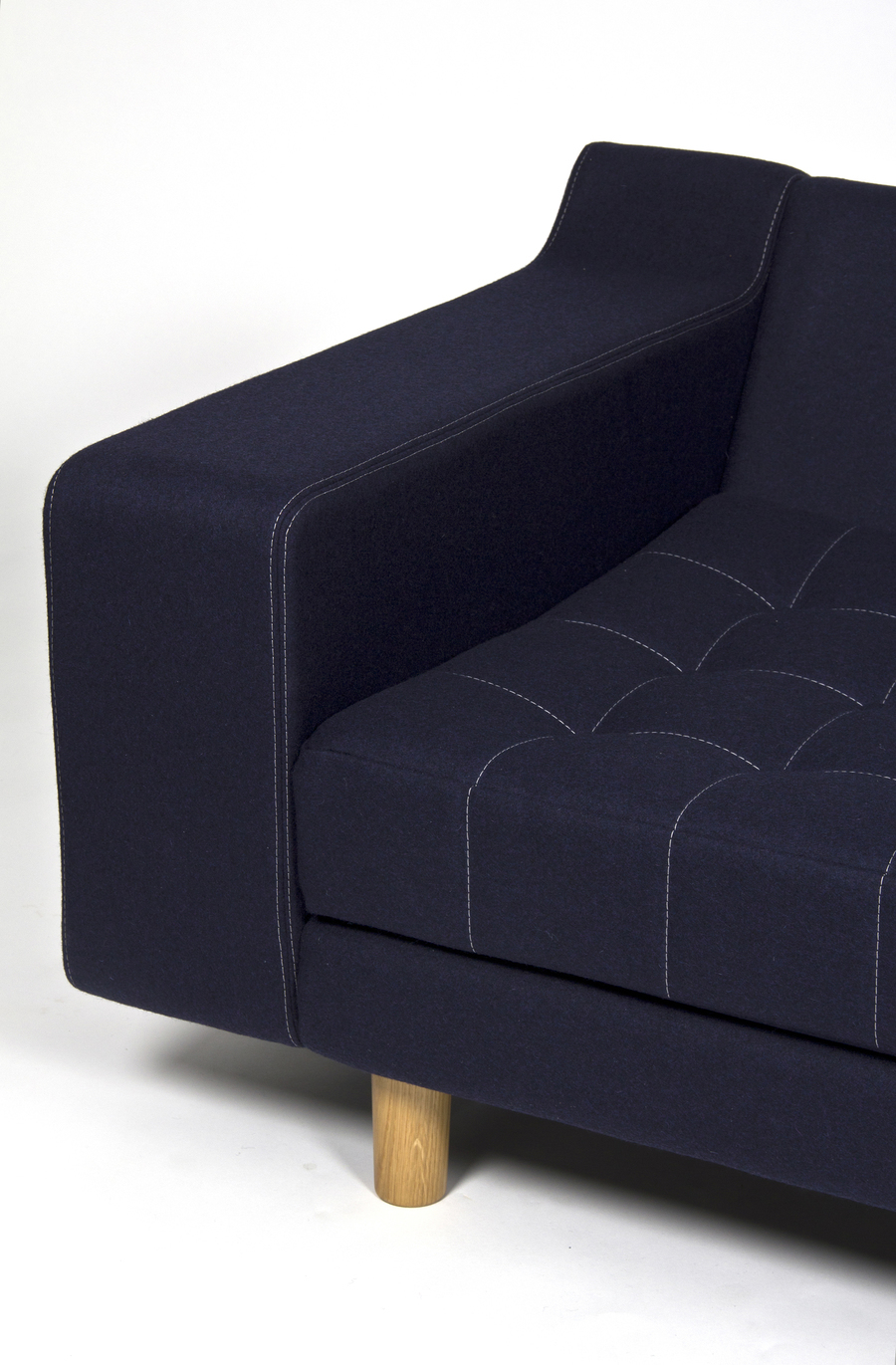 A close-up view from the front of the right side of a navy naughtone Portion Sofa with solid walnut legs and white stitching.